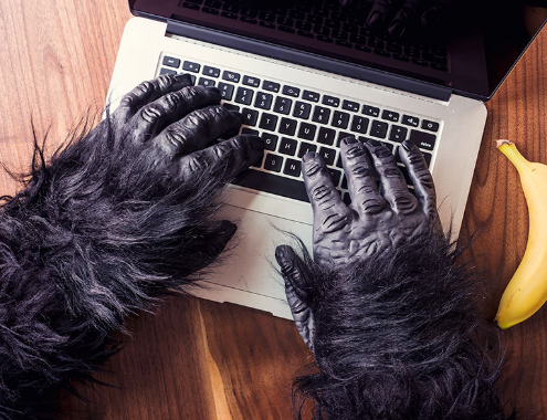 Gratisography gorilla hands on a laptop
