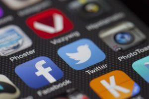 Image of a phone screen with facebook and twitter amongst a number of applications