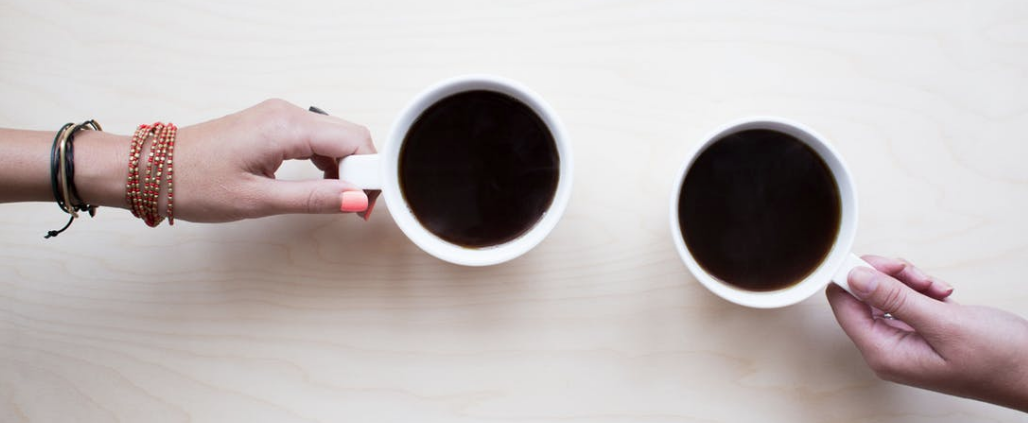 Pexels Image of two coffees held by hands at a meeting
