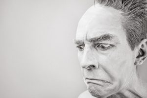 Black and white image of man pulling nervous and inquisitive expression