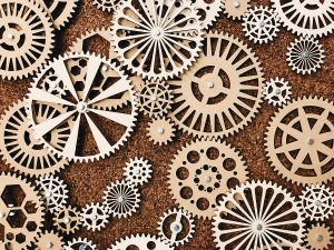 Wooden cogs on a cork background
