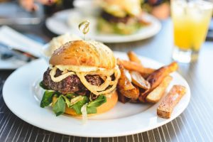 Juicy burger on plate with handcut potato chips