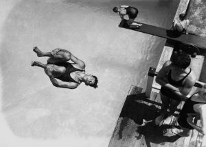 Black and white pool diving scene, a man somersaults
