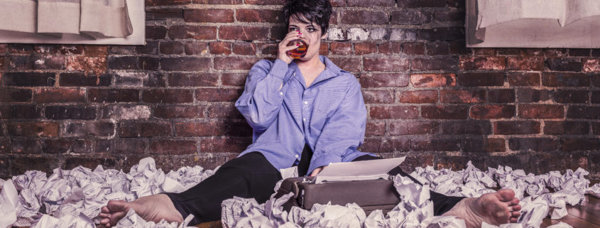 Woman surrounded by rolled up pieces of paper drinking wine
