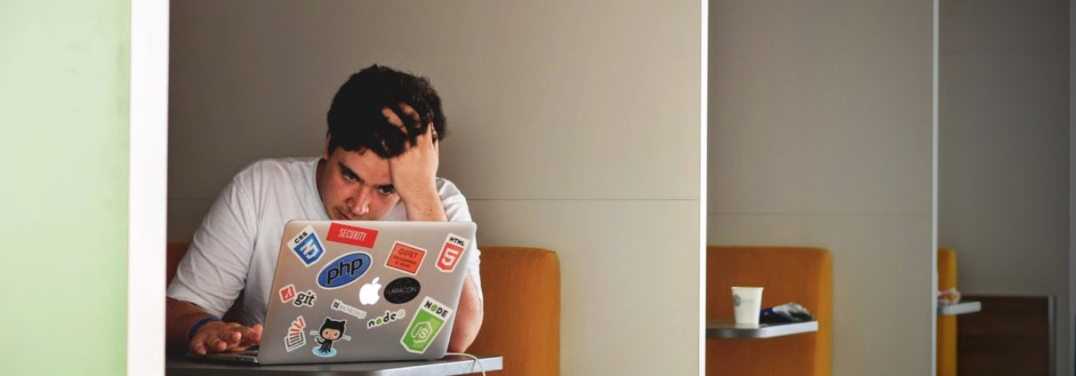 Image of a stressed man looking at a laptop, hand on head
