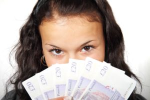 Image of a girl holding £20 notes