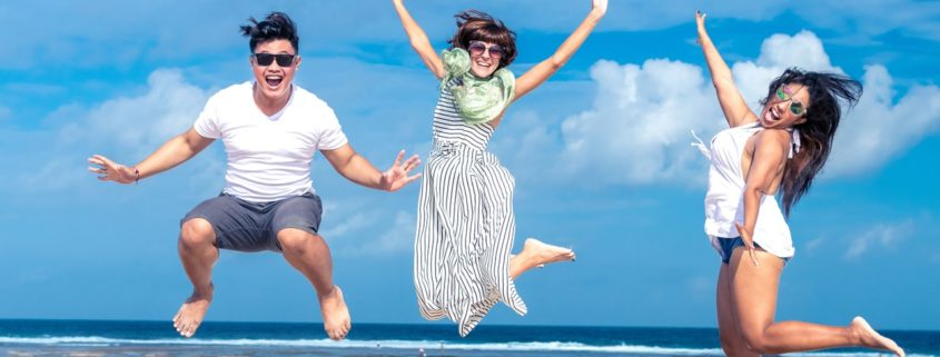 3 people jump in the air happy with a seascape and blue skies behind them