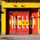 Photo of a brightly coloured building with a painted sign over the door saying hello, this way.