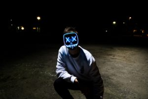Image of a person with a neon lit face mask