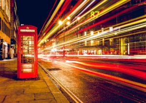 UK city scene of red phone box during the night with a slow capture of a bus passing by