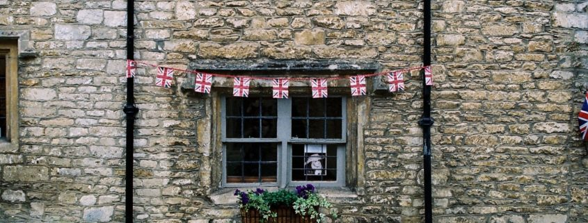 Image of a cobbled brick house with the UK flag bunting on it