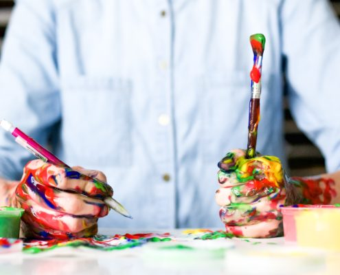 Picture of an artist in a blue shirt with a pencil and paintbrush. Hands and paintbrush is covered in multi-coloured pain