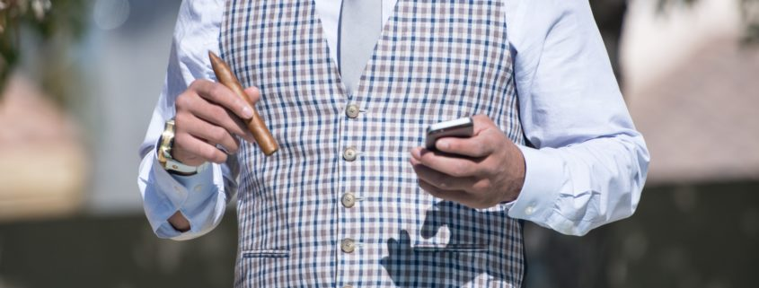 Image of man in luxury waistcoat with a cigar in hand and phone in the other
