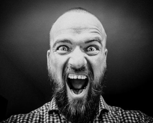 Black and white image of a bearded man shouting