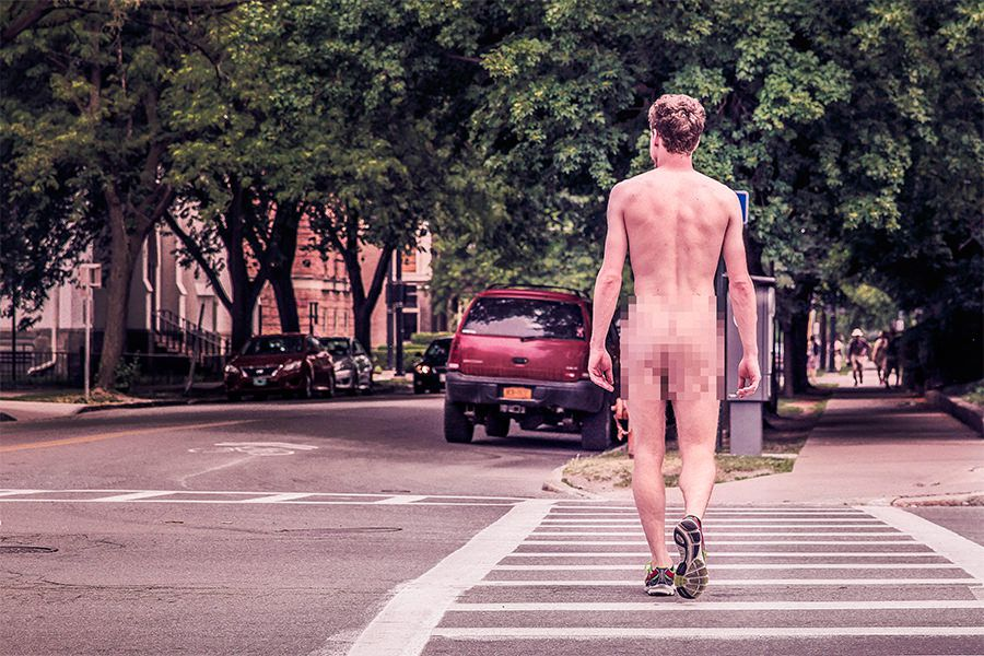 the back of a naked man walking through a street with his buttocks blurred out
