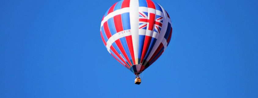 Image of a hot air balloon with a union jack flag on the side on a surrounded by a clear blue sky